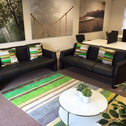 Bellingham House reception area with sofas and coworking area with desks.