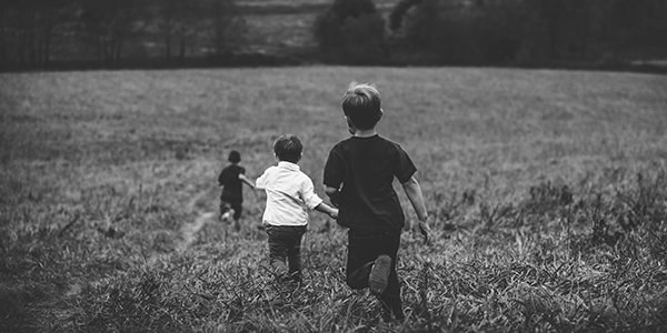 Children running through a field, black and white photo for Self-Employed Summer Holidays blog