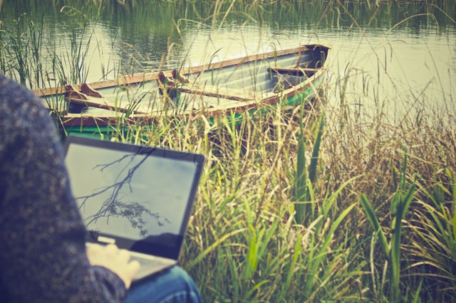 Remote working with a laptop by a rowboat on a river